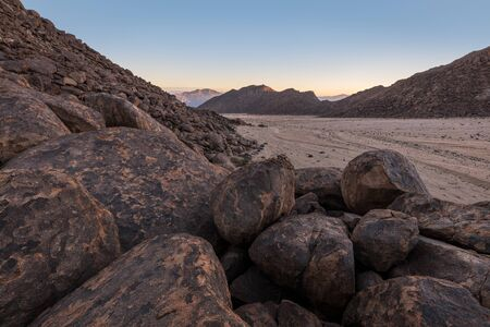 A beautiful arid mountain landscape at sunrise, with fascinating geology and rock formations in the foreground and a mountain range in the background, taken in the Richtersveld, South Africa.