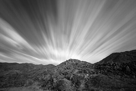 An arid black and white mountain landscape, using a long exposure to blur the fast moving clouds with fascinating geology and rock formations in the background, taken in the Richtersveld South Africa.