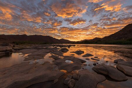 A beautiful landscape of a golden sunset over the mountains and calm waters of the Orange River, with dramatic yellow clouds reflecting in the water's surface, taken in the Richtersveld South Africa.