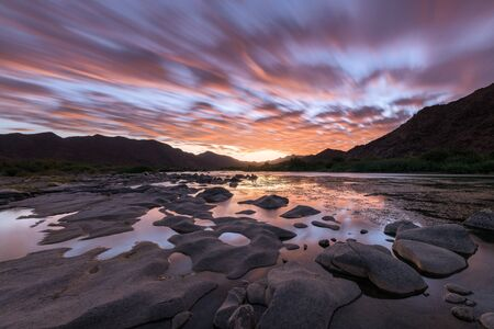 A beautiful long exposure landscape taken after sunset with mountains and the Orange River, with dramatic orange moving clouds reflecting in the water's surface, taken in the Richtersveld South Africa Standard-Bild