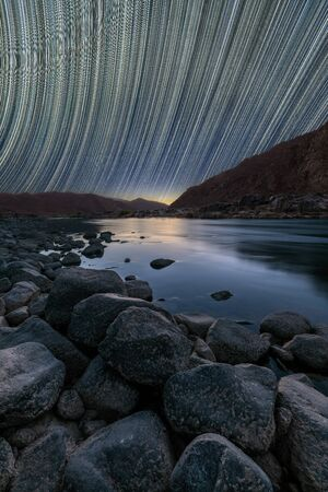 A beautiful vertical night sky landscape on the Orange River with star trails and a mountain range, a deep blue sky and rocks framing the river in the foreground, in the Richtersveld South Africa