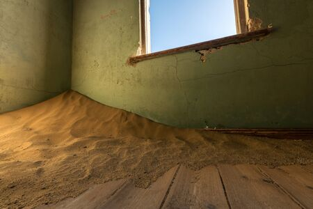 A close up photograph of an old, broken window, with desert sand piling in the corner of an abandoned house, taken in the ghost town of Kolmanskop, Namibia.