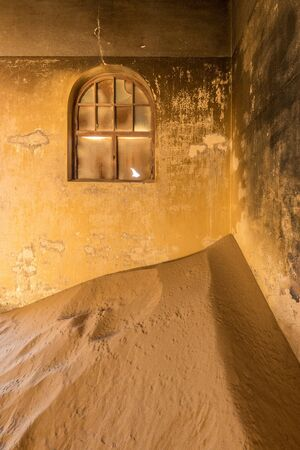 A vertical photograph inside an abandoned house with desert sand piled in the corner and a broken window in the wall, taken in the ghost town of Kolmanskop, Namibia. Stock Photo