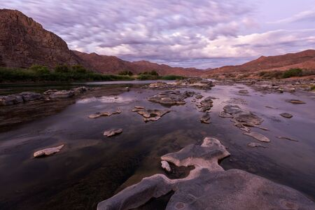 A beautiful landscape taken after sunset with mountains and the Orange River, with dramatic moving clouds reflecting in the water's surface, taken in the Richtersveld National Park, South Africa.