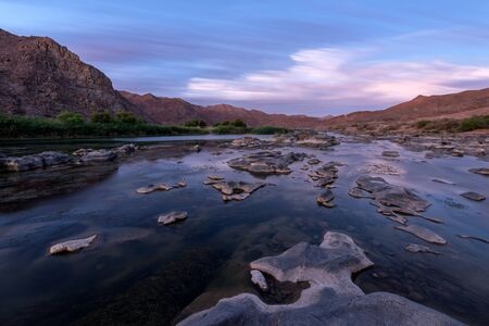 A beautiful long exposure landscape taken after sunset with mountains and the Orange River, with dramatic moving clouds reflecting in the water's surface, taken in the Richtersveld South Africa. Standard-Bild