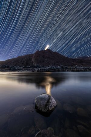 A beautiful vertical night sky landscape with star trails against a deep blue sky and the Moon setting behind mountains, reflecting in the Orange River, taken in the Richtersveld South Africa.