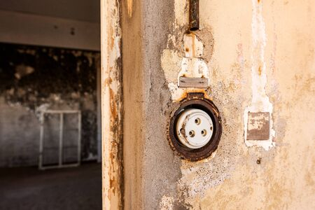 A close up photograph inside an abandoned house of an old electrical socket on a wall, taken in the ghost town of Kolmanskop, Namibia. Standard-Bild