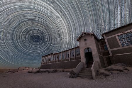 A spooky and dramatic night sky photograph of the old hospital building with circular star trails and desert sand, taken in the ghost town of Kolmanskop, Namibia. Standard-Bild