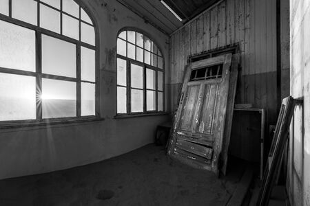 A dramatic black and white photograph inside an abandoned house at sunrise, with a sunburst through broken windows and a door buried in desert sand, taken in the ghost town of Kolmanskop, Namibia. Standard-Bild