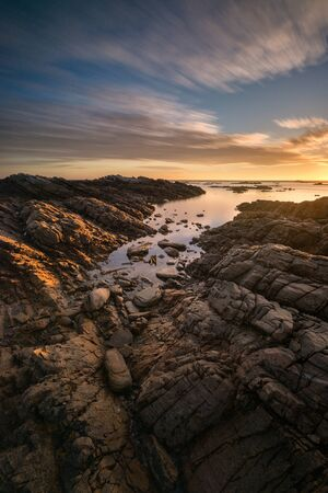 A tranquil long exposure vertical seascape, taken in Port Nolloth, South Africa at sunset with golden reflections, a dramatic cloudy blue sky and rocks in the foreground.