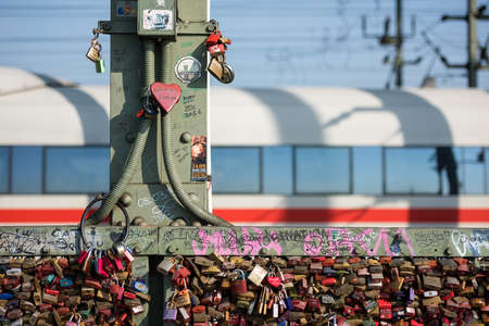 An detailed abstract photograph of the love locks attached to the Hohenzollern Bridge in Cologne, Germany, with a train passing by in the background.