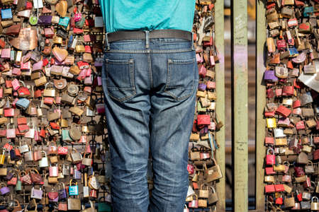 An abstract photograph of a torso of a person standing in front of the hundreds of love locks attached to the Hohenzollern Bridge in Cologne, Germany.