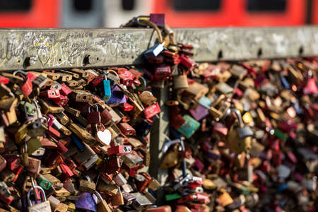 An detailed photograph of the love locks attached to the Hohenzollern Bridge in Cologne, Germany, with a train passing by in the background. Editorial