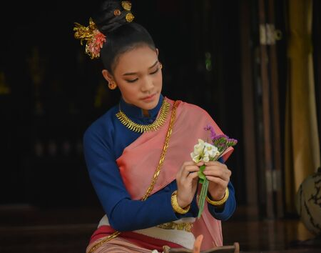 Asian girl dressed in traditional northern Thai dress in Lanna Style Thai House , Chiangmai , Thailand.
