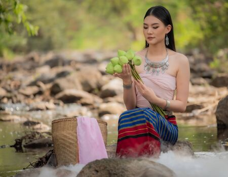 Beautiful woman wearing northern style dress, sitting on the rock in a stream with lotus basket, Chiangmai, Thailand.