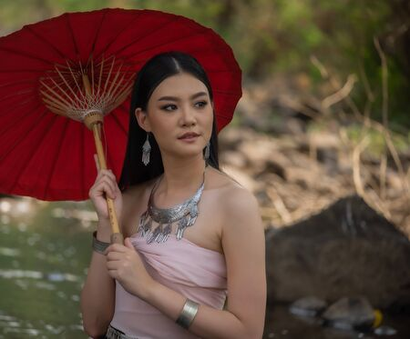 Beautiful woman wearing northern style dress, sitting on the rock  in a stream and holding an umbrella,Chiangmai, Thailand.