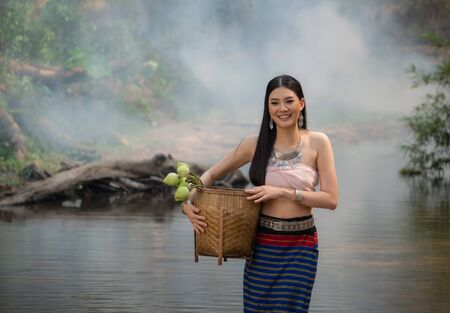 Beautiful woman wearing a northern style dress standing in the stream  with lotus basket, Chiangmai, Thailand.