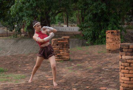 Ancient Thailand martial art called Muay Thai. Thai woman practice Thai kick boxing.