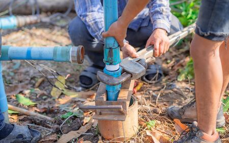 Pipe wrench used for well maintenance.Pipeline to the underground water pipe on a blurred background.