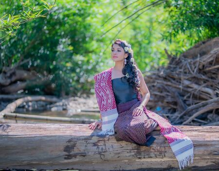 Beautiful Thai women wearing traditional Thai clothes sitting on a log in the river. Woman concept. Stock Photo
