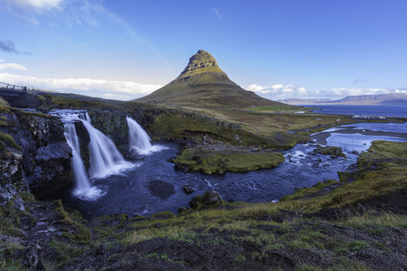 Amazing sunrise the top of Kirkjufellsfoss waterfall with Kirkjufell mountain in the background on the north coast of Icelands Snaefellsnes peninsula taken white a long shutter speed.