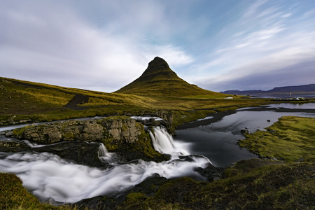 Amazing moonlight at the top of Kirkjufellsfoss waterfall with Kirkjufell mountain in the background on the north coast of Icelands Snaefellsnes peninsula taken white a long shutter speed. Stock Photo