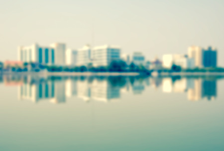 out of focus: Out of focus vintage: a large building located in the center of the city and the reflection in the water.