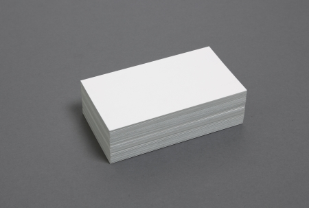 Blank business cards stacked up on a grey background photo