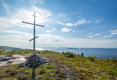 baptize: Christian wooden cross on top of the mountain, island in the white sea