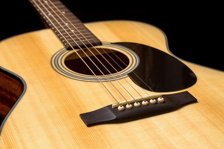 resonator: Yellow acoustic wooden guitar on a black background