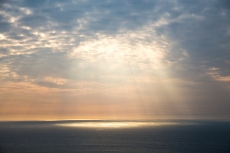 Golden light breaks through the gray sky. The suns rays look through the clouds over the ocean.
