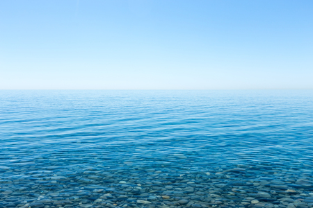Beautiful seascape with a view of the horizon and a cloudless sky. Small smooth stones lying on the sea