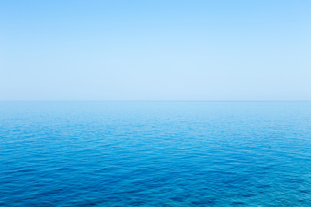 Beautiful seascape without clouds. Perfectly clean smooth sea and clear blue sky