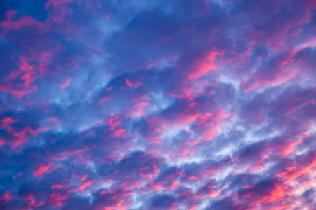 The evening sky is painted red-pink sunset color. Many small purple fluffy clouds.