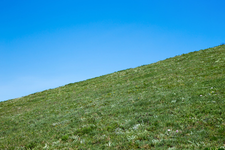 Beautiful landscape, geometry of nature. The mountain slope with green grass on a blue sky background