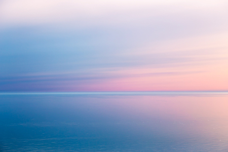 Idyllic seascape with pink evening color. The sky is taken away from the mirror. Blue pink sea background 스톡 콘텐츠