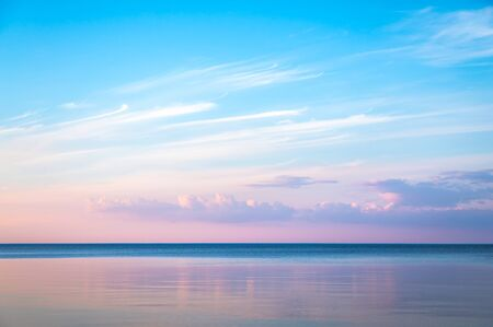 Idyllic seascape with pink evening color. The sky is taken away from the mirror. Blue pink sea background Imagens