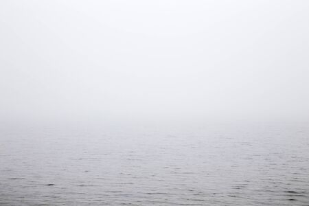 Misty morning over the lake. Gray thick fog over the water surface closes the horizon. Dull day. 스톡 콘텐츠
