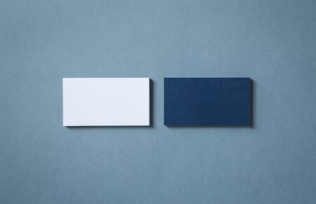 Thick blank double-sided business cards with textured surface stacked up on a gray background