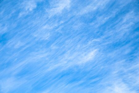 Cloudscape Blue sky background with white clouds. The texture of the sky with translucent light feathery clouds. Diagonal direction.