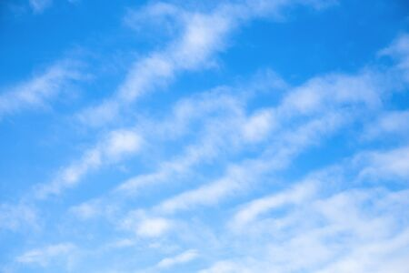 Cloudscape Blue sky background with white clear clouds. The texture of the sky with translucent light feathery clouds. Diagonal direction. Imagens