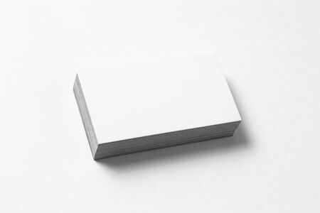 Blank business card on white background. Side view. Standard size. Stylish textured stack of cardboard for personal advertising or corporate design.