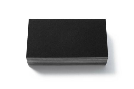 Blank black business card isolated on white background. Front view. Standard size. Stylish textured stack of cardboard for personal advertising or corporate design.