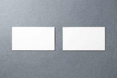 White blank business cards neatly stacked on a gray background. Composition of two cards for layout design. Front and back view.