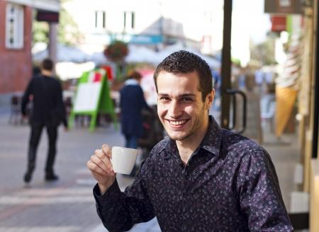 man drinking coffee on the street photo