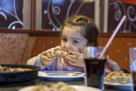 Child eating pizza in restaurant photo