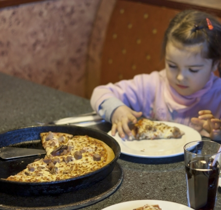 greediness: Child eating pizza in restaurant