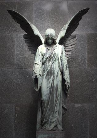 alas de angel: la escultura de un �ngel con fondo oscuro