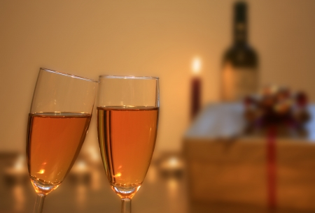 two glasses of champagne with gift and candle photo