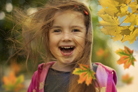 autumn hair: little girl in autumn with falling leaves and hair in wind